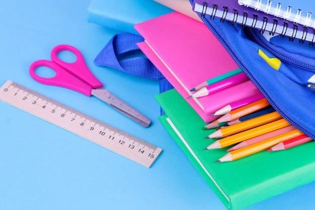 Школьные принадлежности, выпадающие из школьного рюкзака на синем фоне