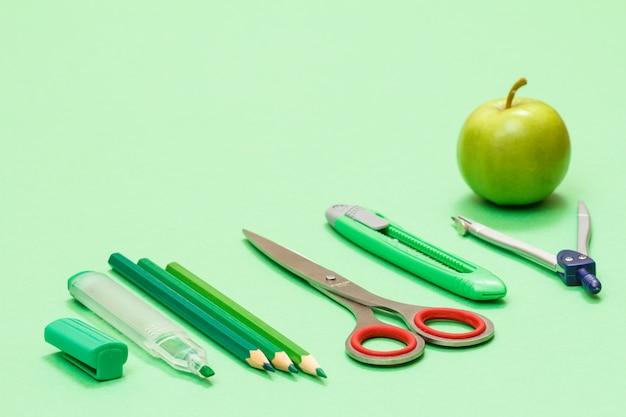 Школьные принадлежности. фломастер, цветные карандаши, ножницы, нож для бумаги, компас и яблоко на зеленом фоне. снова в школу концепции. малая глубина резкости.