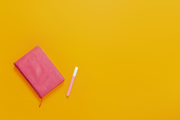 School supplies flat lay on the orange background. pink notebook and colorful marker pens and stickers.