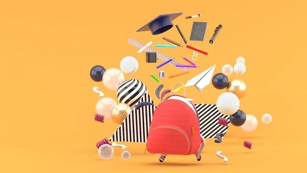 オレンジ色のカラフルなボールに囲まれたランドセルから浮かぶ学用品。 3dレンダー