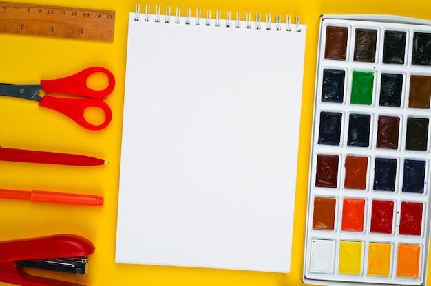 Школьные принадлежности для творчества на желтом фоне.