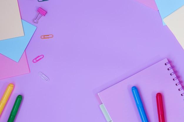 Школьные принадлежности для учебы на розовом фоне. обратно в школу. вид сверху.