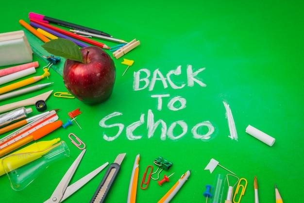 School supplies on green chalkboard