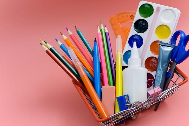Школьные принадлежности в корзине для покупок на розовом фоне. подготовка к школе, покупка канцелярских товаров. обратно в школу.
