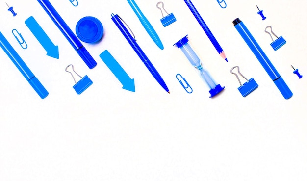 コピースペースのある明るい壁に青と水色の学用品。フラットレイ