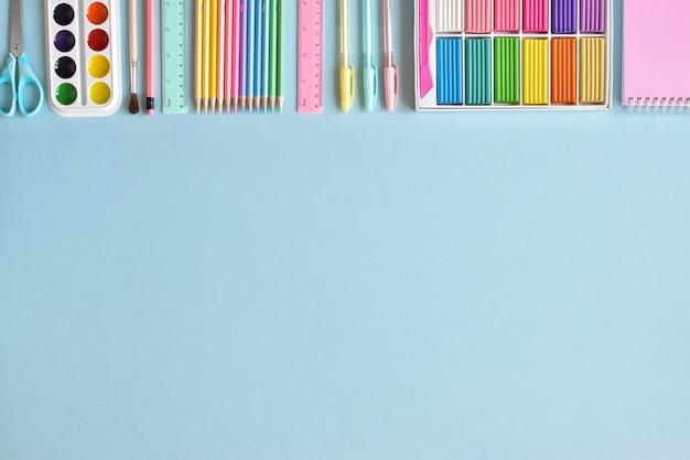 Школьные принадлежности в пастельных тонах на голубой поверхности для текста