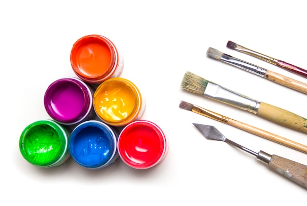 School supplies. jars with colorful art paint and brushes are on a white background.