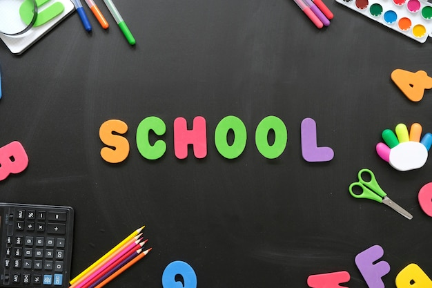 School supplies and letters on black board background