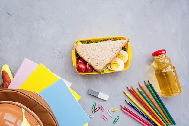 School supplies and lunch box with sandwich and vegetables