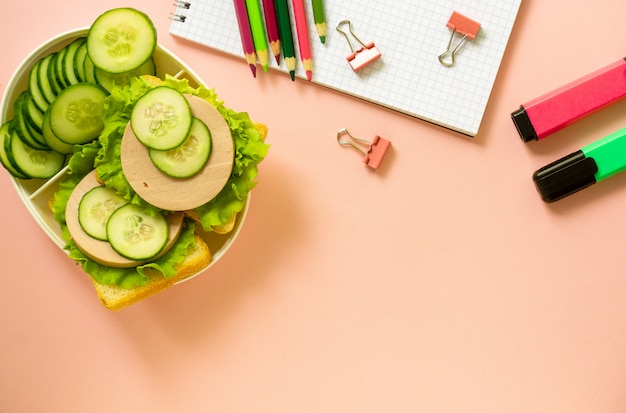 School supplies and lunch box with sausage sandwiches on a pink background