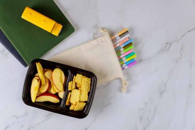 School supplies and lunch box with sliced apple and crackers