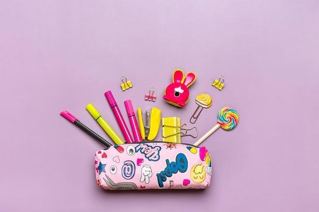 보라색 배경에 학교 용품 돋보기 연필 펜 종이 클립 스테이플러