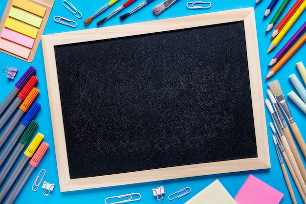 학용품은 중앙에 다채로운 연필 펠트 팁에 검은 칠판 칠판 주위에 프레임을 만듭니다.