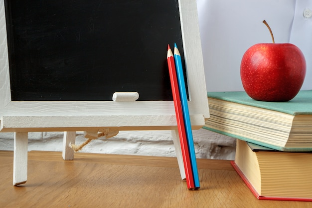 School supplies, miniature chalk board, a stack of books and an apple on the table