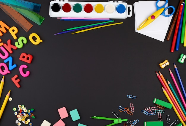 School supplies: multicolored wooden pencils, paper stickers, paper clips