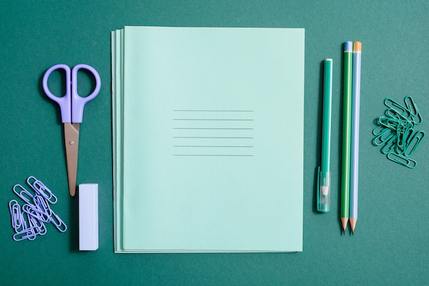 School supplies, notebook, pen and pencil on a green background.
