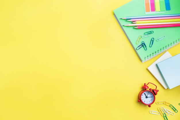 School supplies, notebooks pencils on yellow background with copy space.