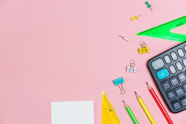 Школьные принадлежности на розовом фоне обратно в школу, калькулятор творческих иллюстраций и канцелярские товары ...