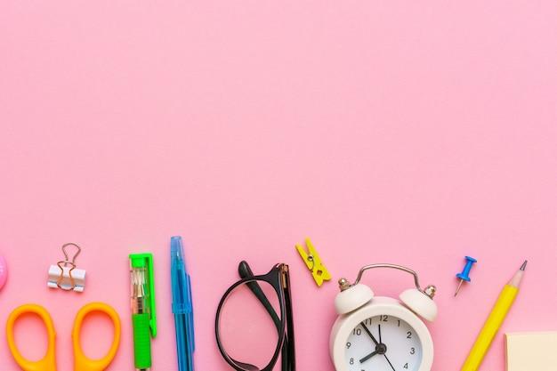 Школьные принадлежности на розовом фоне обратно в школу творческий шаблон иллюстрации белый будильник ...