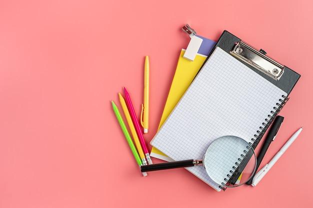 Школьные принадлежности на розовом фоне с копией пространства