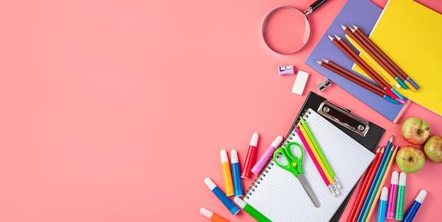 Школьные принадлежности на розовом фоне с пространством для копирования. обратно в школу.