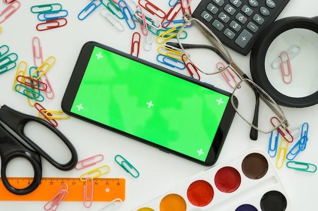 Школьные принадлежности на белом фоне, в центре телефона с зеленым экраном, копией пространства.