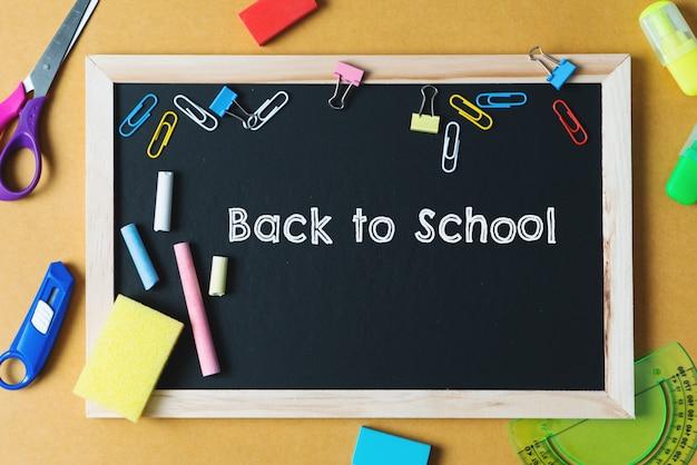 Школьные принадлежности на фоне черной доске. вернуться к концепции школы