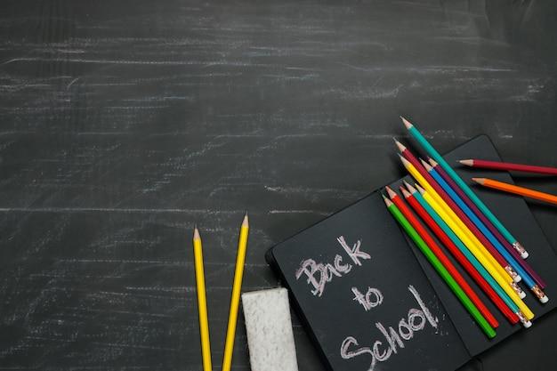 ブラックボードの背景に学用品。学校のコンセプトに戻る。