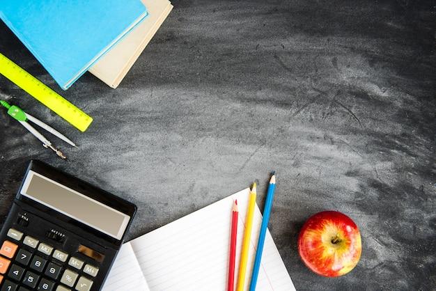 ブラックボードの背景に学用品します。色鉛筆、電卓、ルール、コピーブック。学校のコンセプトに戻る。