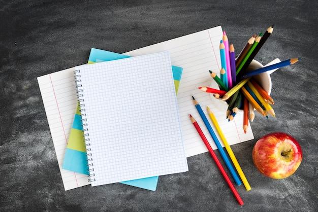 Школьные принадлежности на фоне черной доски. цветные карандаши, калькулятор, правила и тетрадки. снова в школу концепции.