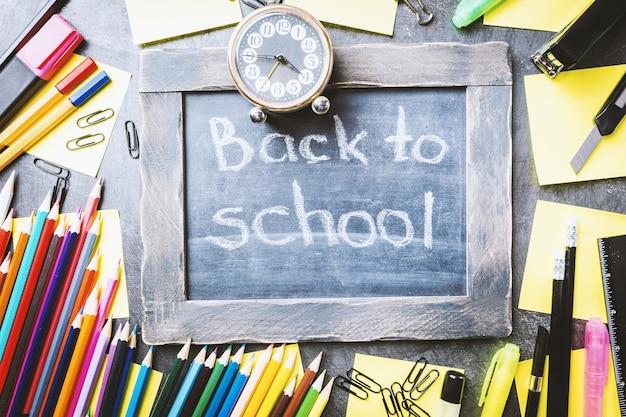 Школьные принадлежности на доске, обратно в школу концепции