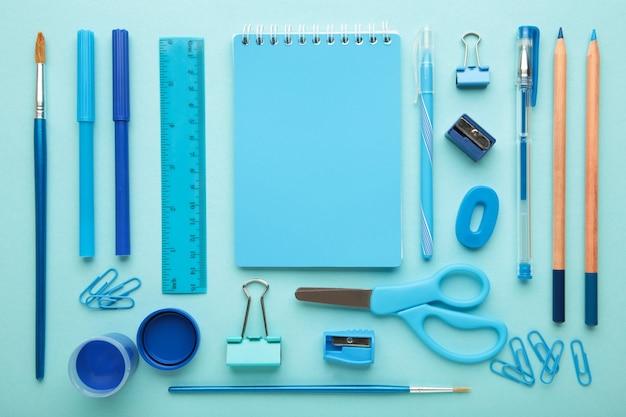 青い背景の学用品。学校に戻る。フラットレイ。上面図