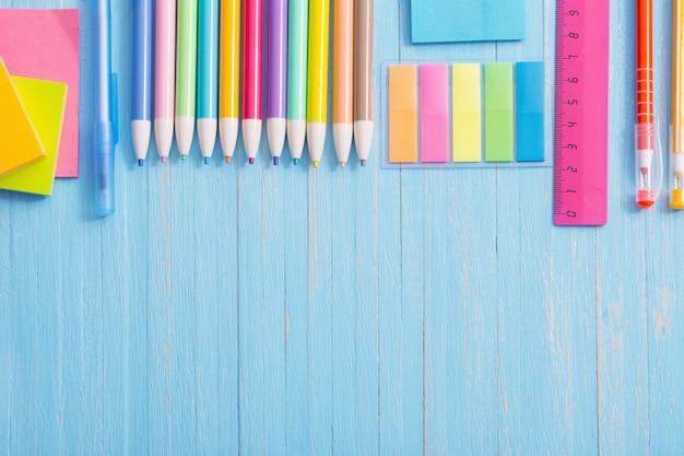 青い木製の背景に学用品
