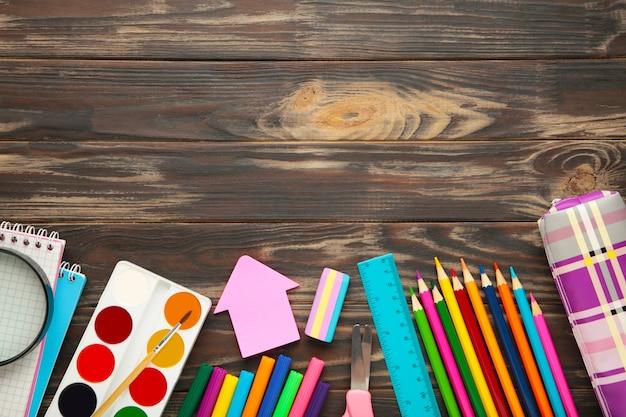 コピースペースとbrpwn木製の背景に学用品。学校のコンセプトに戻ります。上面図。