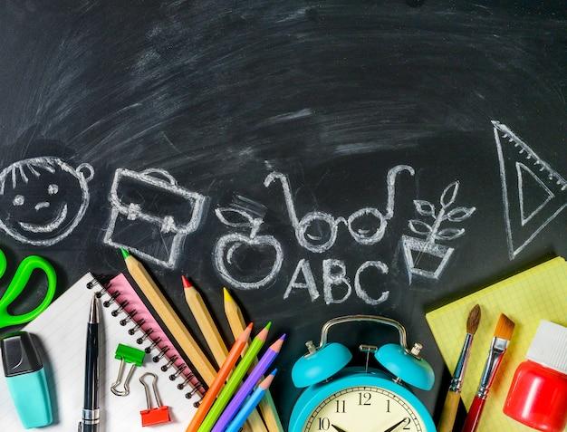 Школьные принадлежности на фоне классной доски с рисунками мелом на нем. скопируйте пространство. снова в школу концепции.