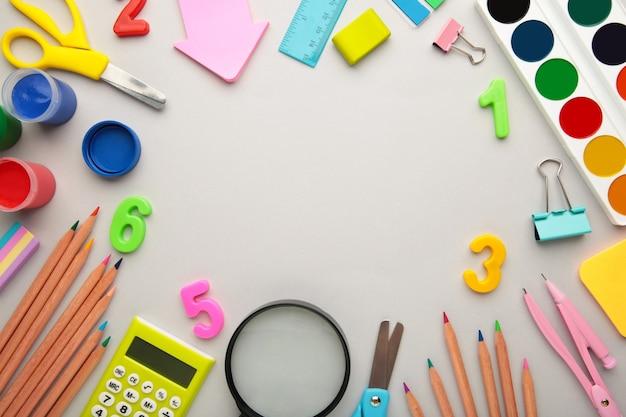 Школьные принадлежности на сером фоне с копией пространства. снова в школу концепции.