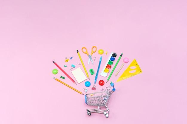 복사 공간 사무실 위의 쇼핑 카트 보기에서 분홍색 배경의 학용품