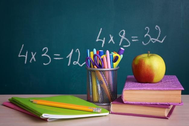 Школьные принадлежности на столе на фоне доски
