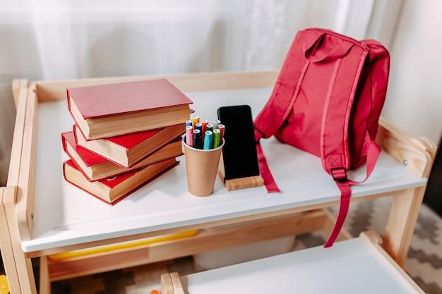 Школьные принадлежности на парте. на белой парте лежали красный рюкзак, белые наушники, тетрадь, большие красные книги, ручки в банке.