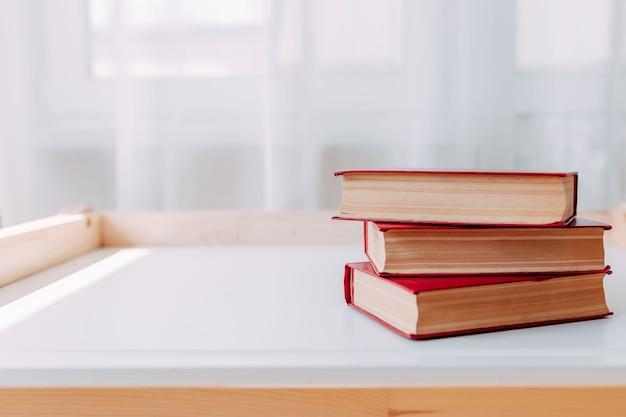 白いテーブルの上の学用品。テーブルの上の大きな赤い本。