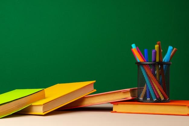 Школьные принадлежности на деревянном столе на фоне зеленой доске