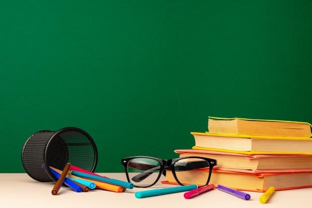 Школьные принадлежности на деревянном столе на зеленой доске