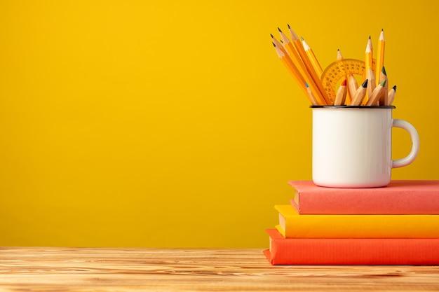 Школьные принадлежности на деревянном столе на желтом фоне