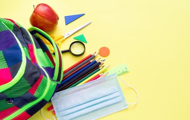 Школьные принадлежности на желтом фоне. снова в школу концепции.