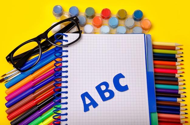 Школьные принадлежности на желтом столе. плоско. вернуться к концепции школы