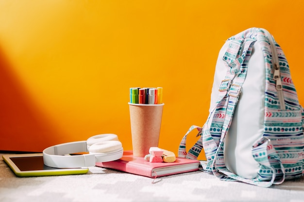 School supplies on the orange background. blue backpack, white headphones, notebook and pens, tablet.