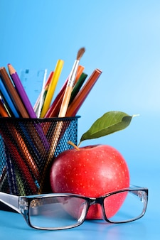 School supplies pencils, pens, ruler, brush, books and apple on blue background