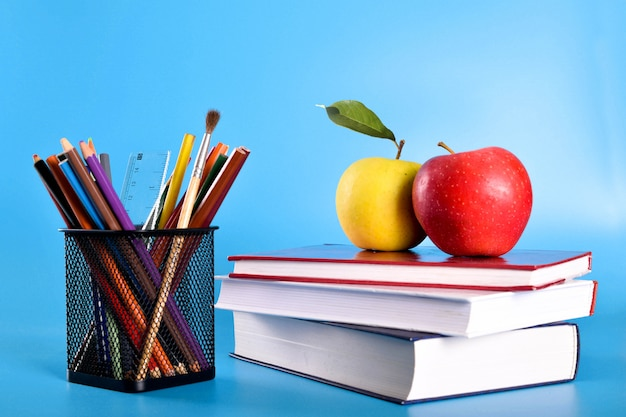 School supplies pencils, pens, ruler, brush, books and apple on blue