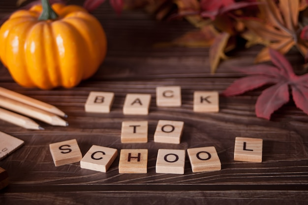 School supplies, pumpkin, autumn leaves and text back to school on the wooden table