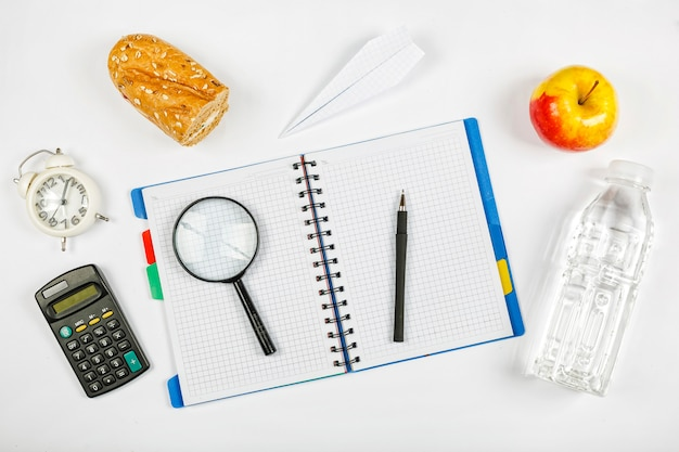 School supplies and a ripe apple is a symbol of new knowledge and ideas on the white background